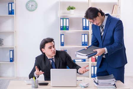 Capo e il suo assistente di sesso maschile che lavorano in ufficio