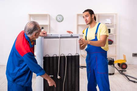 Two contractors repairing fridge at workshop