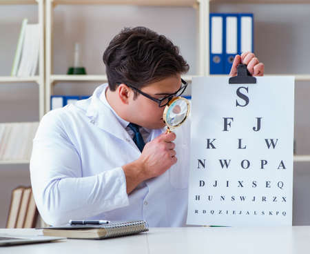 The doctor optician with letter chart conducting an eye test check