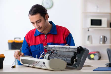 Young repairman repairing air-conditioner at warranty center Stock fotó