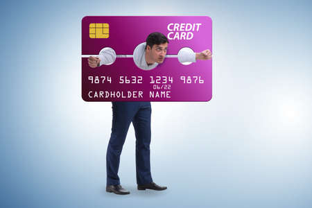 Businessman in credit card burden concept in pillory Banque d'images