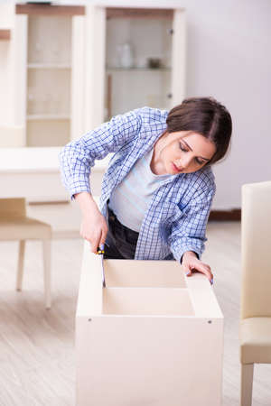 Young beautiful woman assembling furniture at home