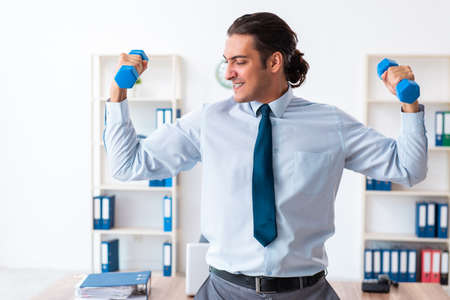 Young handsome employee doing sport exercises at workplace