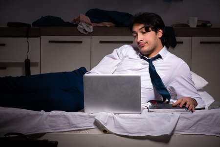 Young employee working at home after night shift