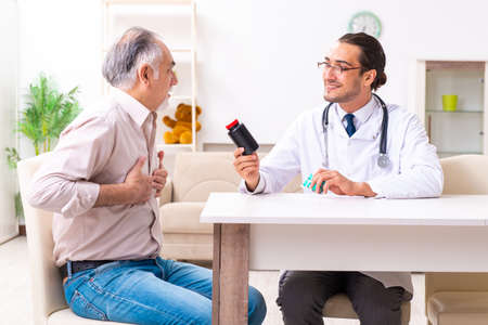 Young male doctor visiting old patient at home