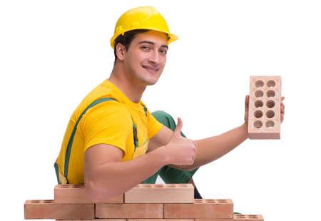 Der gutaussehende Bauarbeiter, der eine Backsteinmauer baut