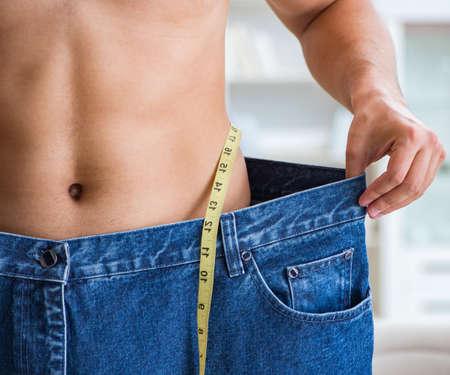 El hombre de pantalones de gran tamaño en concepto de pérdida de peso