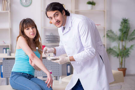 Young arm injured woman visiting young doctor traumatologist