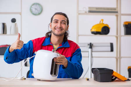 Young male contractor repairing toaster at workshop Stock Photo
