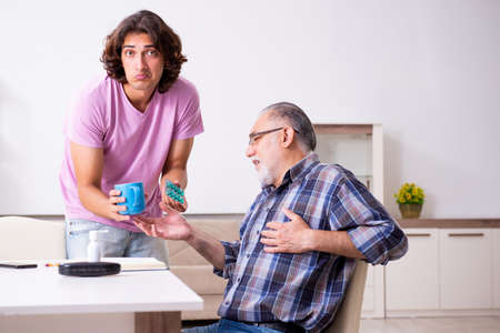 Young student and his old grandpa at home Stok Fotoğraf