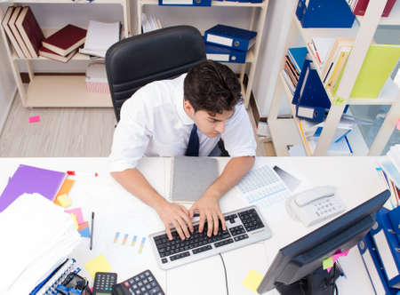 Businessman working in the office with piles of books and papers doing paperwork