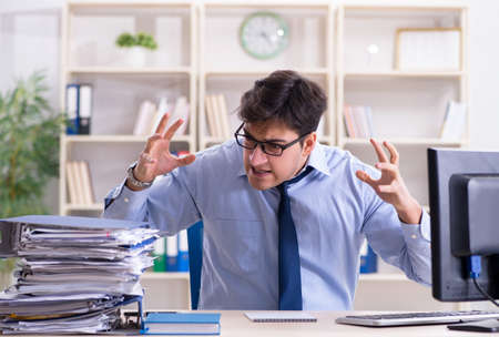 Tired businessman with too much paperwork Stock Photo