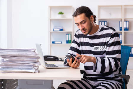 Young employee feeling like prisoner at work