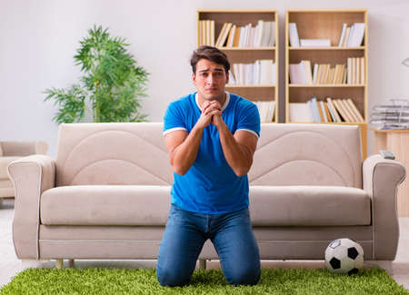 Man watching football at home sitting in couch Banque d'images