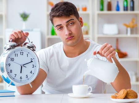 Man with alarm clock falling asleep at breakfast Stok Fotoğraf