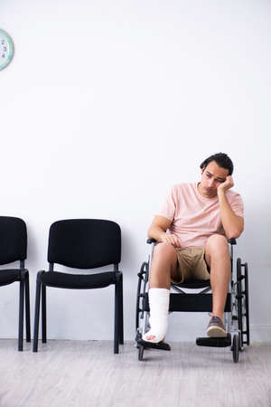 Young injured man waiting for his turn in hospital hall