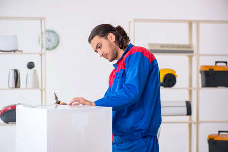 Young male contractor repairing refrigerator at workshop Stock Photo
