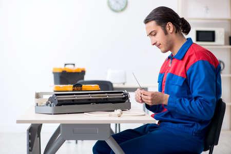 Young repairman repairing air-conditioner at warranty center Stockfoto