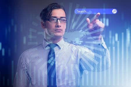 Search concept with businessman pressing button Standard-Bild
