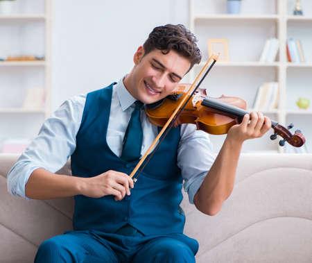 Young musician man practicing playing violin at home