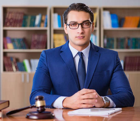 Handsome judge with gavel sitting in courtroom Banque d'images