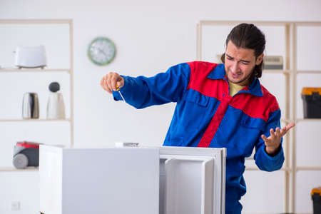 Young male contractor repairing refrigerator at workshop Stockfoto