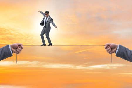 Businessman walking on tight rope Stock Photo