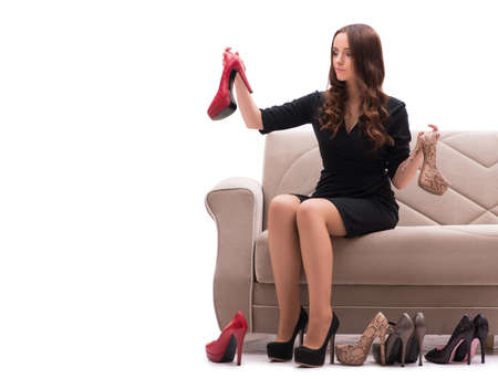 Woman having difficult choice between shoes Imagens