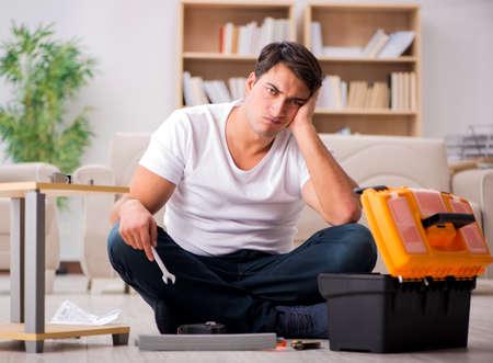 Man assembling shelf at home Stock Photo