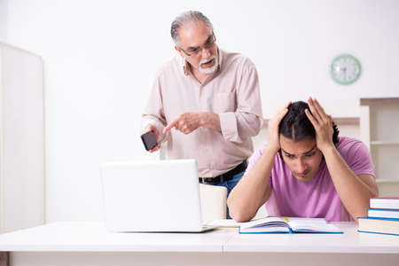 Old father helping his son in exam preparation