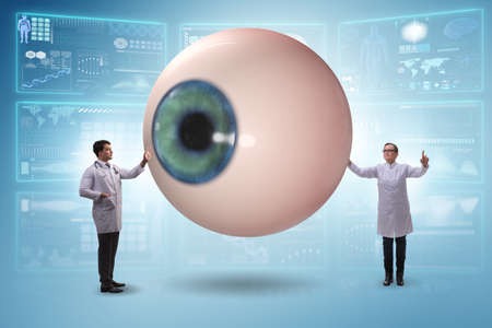Doctor examining giant eye in medical concept Banco de Imagens