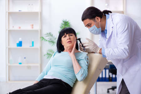 Old woman visiting young doctor laryngologist