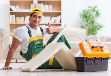 Worker repairing furniture at home Banque d'images