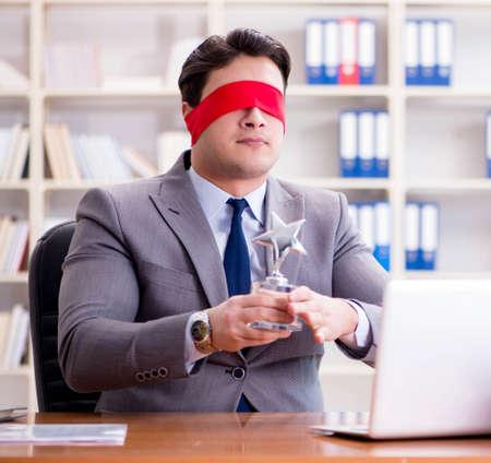 Blindfold businessman sitting at desk in office Stockfoto