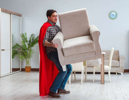 Super hero moving furniture at home Banque d'images