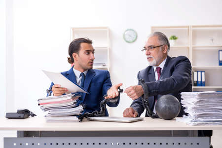 Two male employees unhappy with excessive work Stock Photo