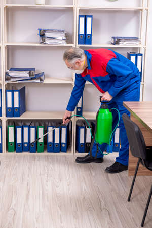 Old professional contractor doing pest control in the office 写真素材