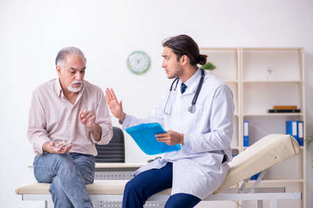 Young male doctor and old patient in antismoking concept