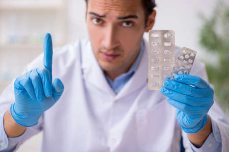 Young male lab assistant in drug synthesis concept
