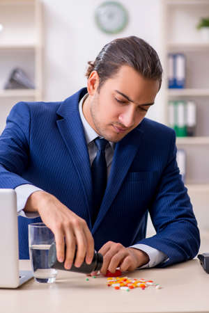 Young male employee and a lot of pills on the desk Stock fotó