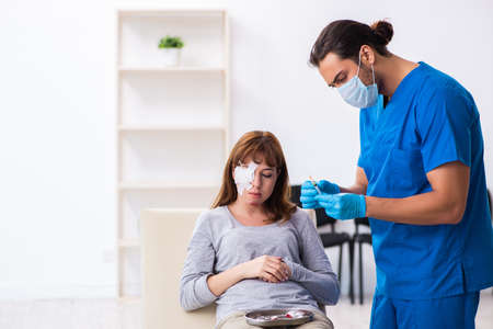 Young head injured woman visiting young male doctor