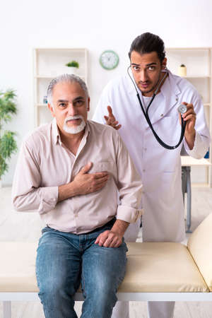 Old man visiting young male doctor cardiologist Stock Photo