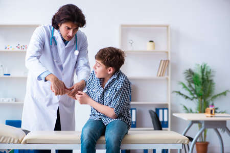 Hand injured boy visiting young male doctor