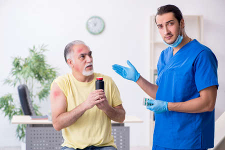 Injured old man visiting young male doctor traumatologist