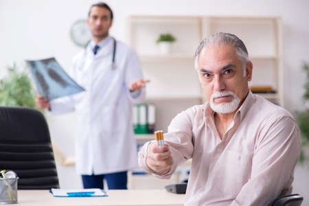 Young male doctor and old patient in antismoking concept Foto de archivo