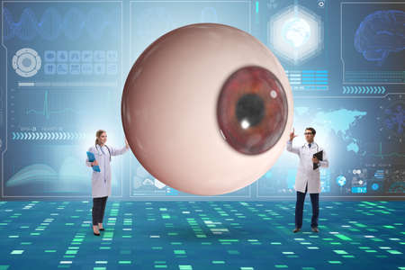 Doctor examining giant eye in medical concept Zdjęcie Seryjne