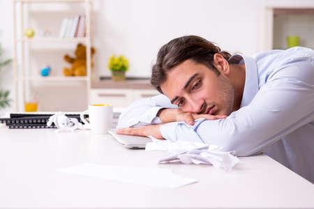 Junger männlicher Geschäftsmann, der zu Hause arbeitet