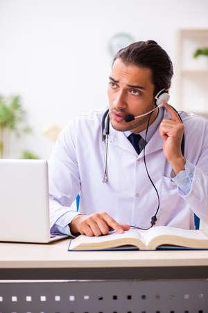 Junger Arzt hört Patienten während der Telemedizin-Sitzung zu Standard-Bild