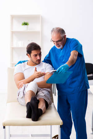 Leg injured man visiting old doctor in first aid concept Imagens