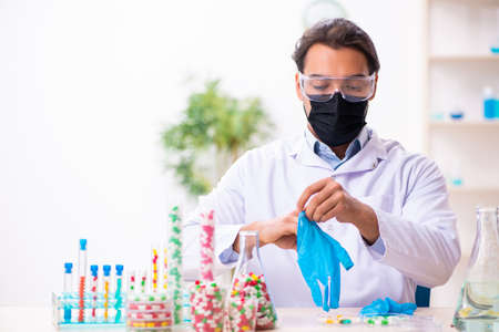 Young male chemist in drug synthesis concept